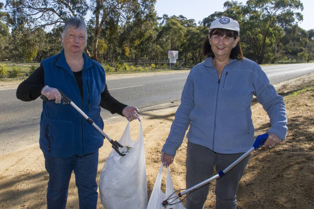 Stawell residents Judy McPhee and Karen Jenkins collecting rubbish on Sloane Street, Stawell. Picture: PETER PICKERING